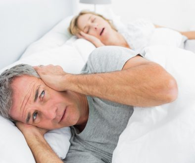 Woman snoring in bed with distressed partner